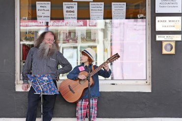 Master storyteller, Eddie Lenihan, pictured watching Milo McCarthy, aged 10, busking outside his parents book store, as part of the festivities of the Mid-May Festival in Midleton at the weekend. Pic: Diane Cusack